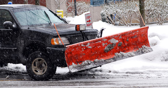 snow plow truck plowing a road
